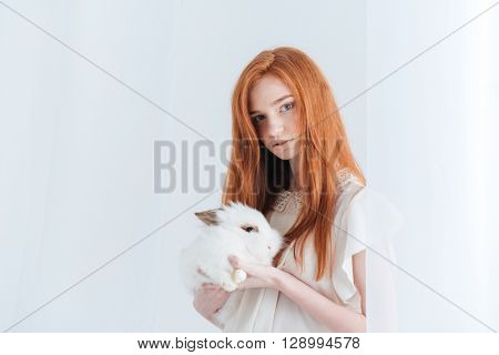 Attractive redhead woman holding rabbit isolated on a white background and looking at camera
