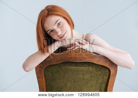 Happy redhead woman sitting on the chair and looking at camera isolated on a white background
