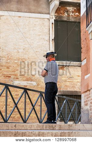 VENICE ITALY - MAY 27 2015: Gondolier in traditional uniform standing lonely and waiting for tourists on the street of Venice Italy