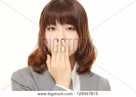 Japanese businesswoman making the speak no evil gesture