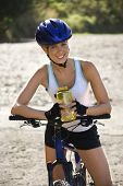 Caucasian mid-adult woman wearing bicycle helmet, sitting on bycycle, holding water bottle, looking