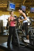 Prime adult Caucasian female on elliptical machine at gym with trainer.