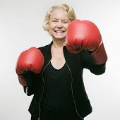 Caucasian senior woman wearing boxing gloves and throwing punch at viewer.