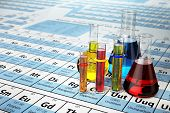 Science chemistry concept. Laboratory test tubes and flasks with colored liquids on the periodic tab poster