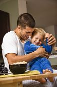Caucasian man tickling toddler son in kitchen.