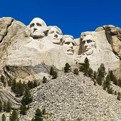 Mount Rushmore National Memorial with mountain and trees.