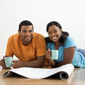 African American male and female couple with architectural  blueprints drinking coffee.