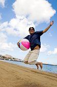 stock photo of beach-ball  - young man having joy at the beach with a beachball - JPG