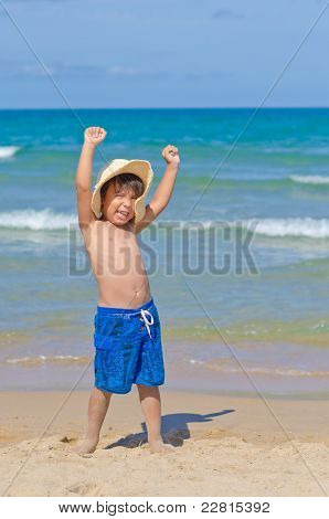 Child In The Beach In A Playful And Happy Atitude