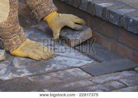 Builder Laying Blue Paving Bricks