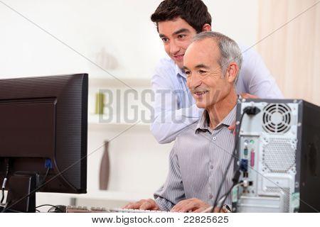 Young man teaching an elderly man computer skills