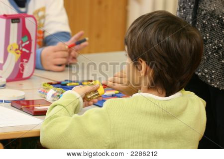 Young Girl Sharpening A Pencil