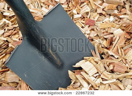 mulch and black shovel