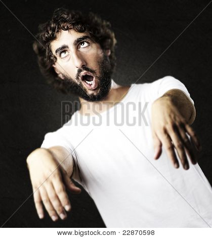 young man imitating a zombie against a grunge wall