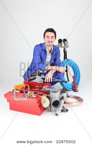 Plumber with a variety of tools and material