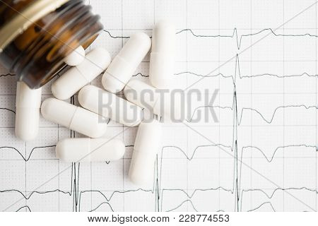 poster of White Pills In Jar On Paper Cardiogram With Copy Space, Flat Lay, Overhead View