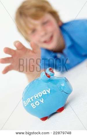 Young boy reaching for piggy bank