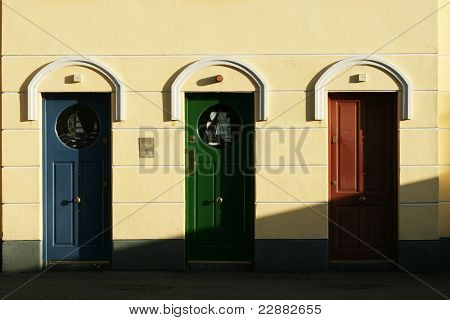 Apartment building with blue,green and brown colored doors