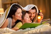 people and family concept - happy mother, father and little daughter reading book with torch light i poster