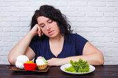 Young Upset Overweight Woman Bored Of Diets Choosing Between Healthy And Junk Food. Dieting, Healthy poster