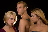 image of promiscuous  - Portrait of a man in between two woman one woman looking at the other to show jealousy - JPG