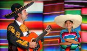 Mexican mariachi charro man and poncho Mexico girl with serape blurred background [Photo Illustratio