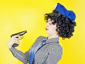 A Girl With A Gun Holding A Gun To Her Head, Pretending To Be Jokingly Timidly Staring At The Barrel poster