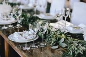 Decorated Elegant Wooden Wedding Table In Rustic Style With Eucalyptus And Flowers, Porcelain Plates poster