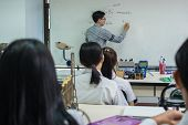 Asian Teacher Giving Lesson Over The The Physics Formular With Thailand Text Language On White Board poster