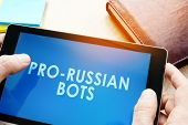 Man Holding Tablet With Words Pro-russian Bots. Russian Internet Propaganda Concept. poster