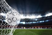 Soccer Ball Pierces The Soccer Goal At The Stadium During A Night Match. 3d Rendering poster