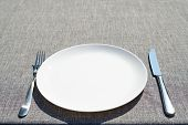 Empty Ceramic Round Plate And Cutlery On Grey Tablecloth, Copy Space. Dinner Plate Setting. White Pl poster