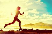 Summer fitness healthy active woman running on beach against sun flare at sunset. Runner athlete spo poster