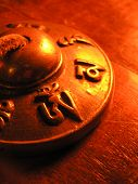 image of tantric  - close up shot of a tibetan bell in candle light showing the mantra - JPG
