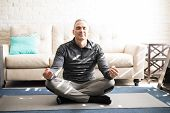 Portrait Of Healthy Mature Man Sitting Crossed Legged On Fitness Mat And Meditating In Lotus Yoga Po poster