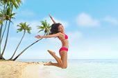Beach fun summer vacation under the sun joyful happy bikini woman jumping of joy on Tahiti luxury tr poster