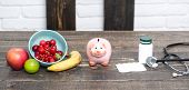 Piggy Bank With Fruit, Medicine And Stethoscope On Table. Medical Insurance Concept. Medicine, Pills poster
