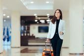 Elegant Business Woman with Travel Trolley Luggage in Hotel Lobby poster