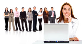 stock photo of latin people  - business team in the background with a businesswoman in an office laptop computer at the front  - JPG