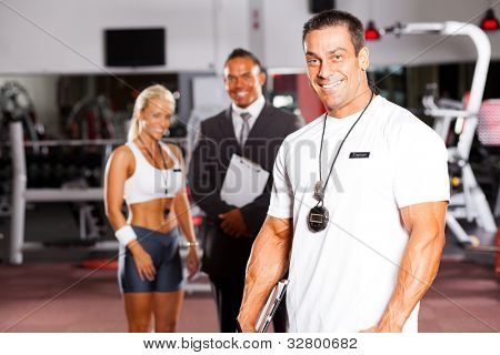 handsome male gym personal trainer in front of colleagues