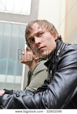 Tough Guys. Portrait Of Two Man Standing On Balcony