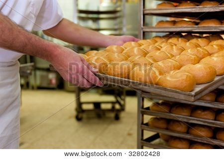 baker standing in his bakery in the morning and is baking bread or buns