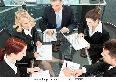 Business people - meeting in an office, the businesspeople are discussing a document
