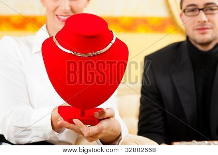 Man giving his wife a necklace as a gift, the necklace is still hanging on the bust
