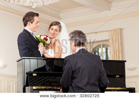 Bridal couple in front of a piano, the pianist is playing a waltz