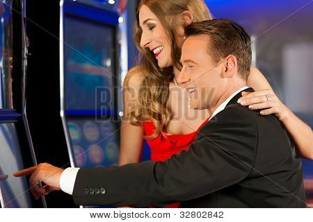 Couple in Casino on a slot machine winning and having fun