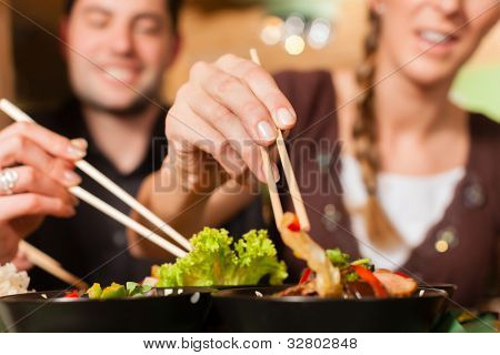 Young people eating in a Thai restaurant; they eating with chopsticks