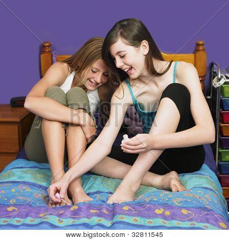 Teenaged girl painting friend's toenails