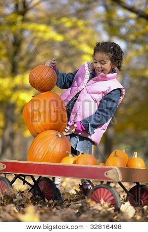 African girl trying to stack pumpkins