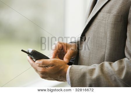 African businessman dialing cell phone